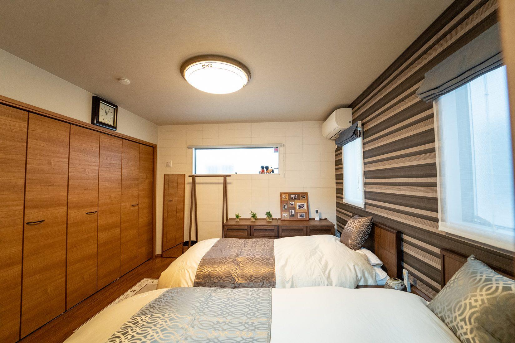 1階の寝室はベッドメイキングがホテル級。毎日きちんと整えているそう。オプション工事で壁を撤去し大きな1室にしている。